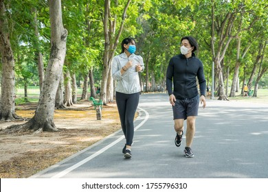 Couples wear masks to protect the corona virus and in jogging in the park together during exercise for health. Sport New normal and Health concept.
