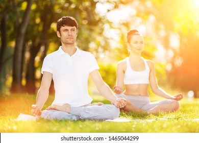 Couples Yoga, man and woman doing yoga exercises, meditate in sunny the park. Yoga outdoor. Concept of healthy lifestyle and relaxation. Yoga meditation in nature. Couple practicing on the grass
