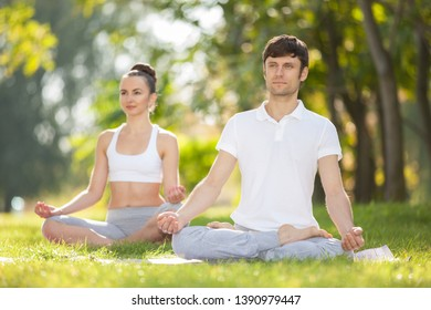 Couples Yoga outdoor. Man and woman doing yoga exercises, meditate in the park. Concept of healthy lifestyle and relaxation. Meditation in nature. Couple practicing yoga on the grass at summer season
