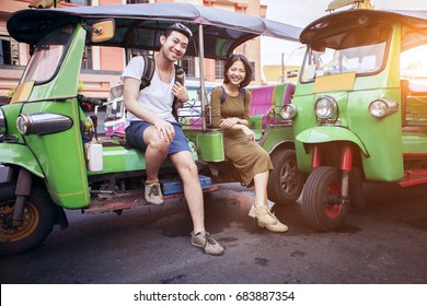 couples of young traveling people sitting on tuk tuk bangkok thailand