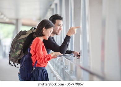 couples of younger traveling man and woman looking to traveler guide book on location