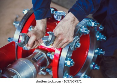 Coupling flange. The worker tightens the bolts on the red coupling sleeve with a wrench. Close-up