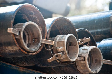 Couplings and drill casings are lined up ready for use at a water drilling site.