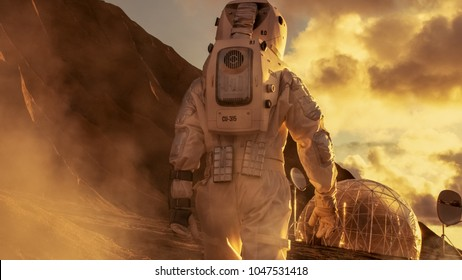 Courageous Astronaut in the Space Suit Explores Red Planet Mars Covered in Mist. Shelter in background. Space Travel, Colonization Concept.