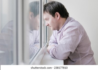 Courageous middle age man looking at the window