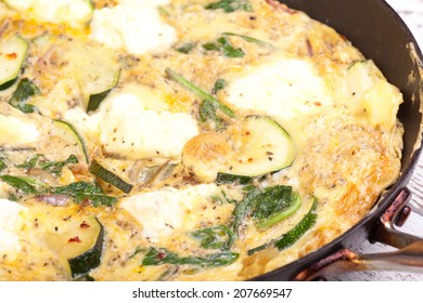 courgette, spinach and ricotta cheese omlet in frying pan