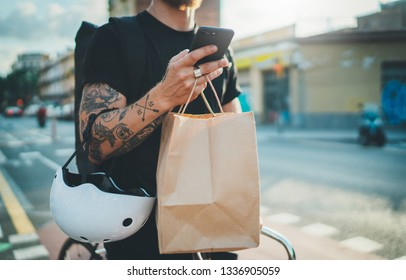 Courier bicycle delivery food service at home. Tattooed Man courier using a map app on mobile phone to find the delivery address in the city.
