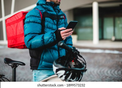 Courier bicycle delivery food service at home.  Man courier using a map app on mobile phone to find the delivery address in the city.Food, delivery, courier, bike, 4g