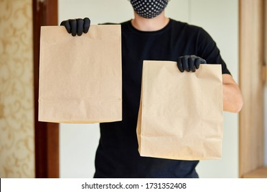 Courier in black hold go box food, delivery service, Takeaway restaurants food delivery to home door. Stay at home safe lives from coronavirus outbreak. Contactless delivery service under quarantine. - Shutterstock ID 1731352408