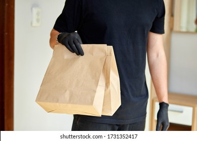 Courier in black hold go box food, delivery service, Takeaway restaurants food delivery to home door. Stay at home safe lives from coronavirus outbreak. Contactless delivery service under quarantine. - Shutterstock ID 1731352417