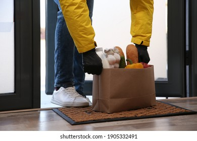 Courier bring paper bag with food to doorway, closeup. Delivery service during quarantine due Covid-19 outbreak