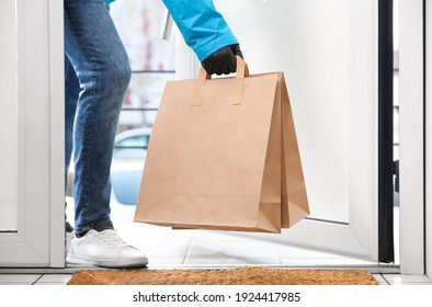 Courier bring paper bags with takeaway food to doorway, closeup. Delivery service during quarantine due Covid-19 outbreak