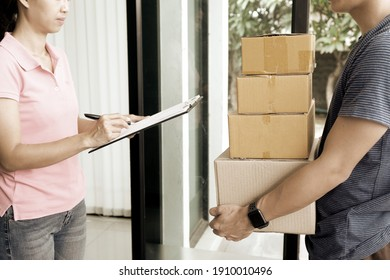 The courier is bringing the box to the customer from the delivery truck to the customer's location.