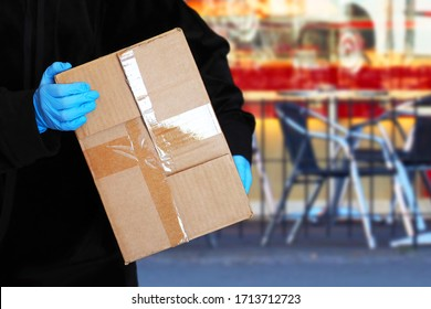 Courier with cardboard box goes down the street, hands in gloves. Delivery of goods during quarantine, package