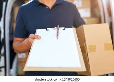 Courier with clipboard and cardboard boxes