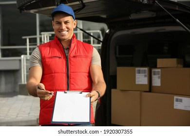 Courier with clipboard near car full of packages outdoors