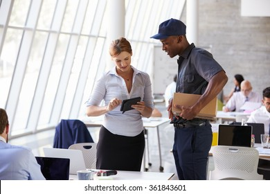 Courier Collecting Package From Businesswoman In Busy Office