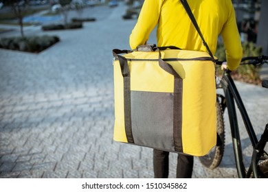 Courier delivering food in a yellow thermo bag with a bicycle in the city, close-up focused on the bag with copy space