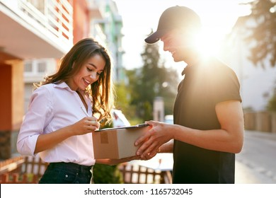 Courier Delivering Package To Woman, Client Signing Document