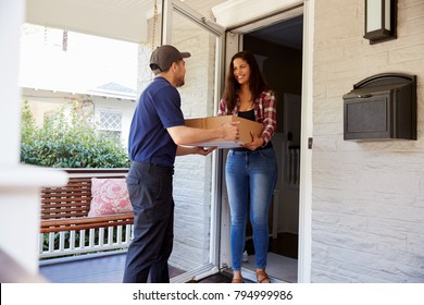 Courier Delivering Package To Woman At Home