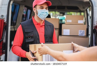 Courier delivering packages with truck while wearing protective face mask for coronavirus prevention - Focus on man worker