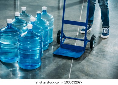 Courier with delivery cart standing by water bottles