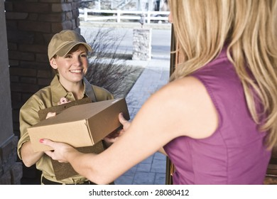 Courier or delivery driver delivering package to a woman at home