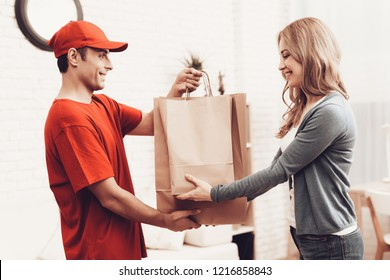 Courier Delivery. Flowers Deliveryman. Man with Box is Funny Accessory. White Interior. Deliveryman Arab Nationality. Courier in Orange Clothes. Express Delivery. Gives Paper Package. Paper Package.
