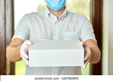 Courier, delivery man in medical latex gloves and mask safely delivers online purchases in white box to the door during the coronavirus epidemic, COVID-19. Stay home, safe concept.