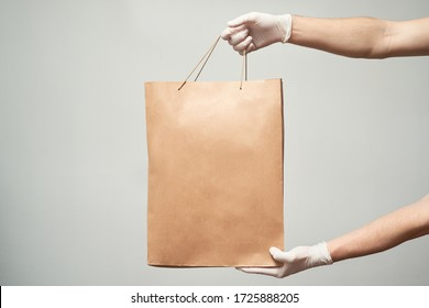 Courier, delivery man in medical latex gloves safely delivers online purchases in brown paper bags to the door during the coronavirus epidemic. Stay home.