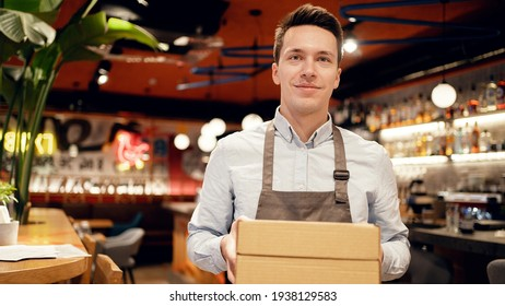 courier delivery is received by the restaurant employee. Sending pizza lunch in a package to your home. Work in a small restaurant in the city center. Smiles favorite work