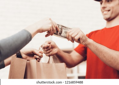 Courier Delivery. Worker Man Arab Nationality. White Interior. Deliveryman Arab Nationality. Courier in Orange Clothes. Express Delivery. Gives Paper Package. Paper Package. Womab Give Cash.
