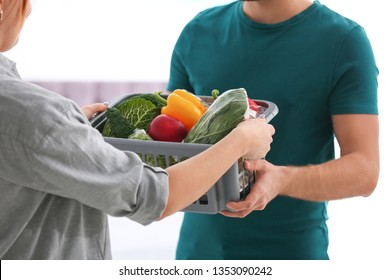Courier giving plastic crate with products to customer at home, closeup. Food delivery service