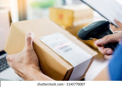 Courier hands Business woman work at home office checking parcel package box by keying machine track tools before ship and documents data.