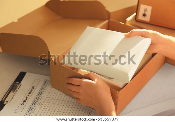 Courier hands packaging parcel at table