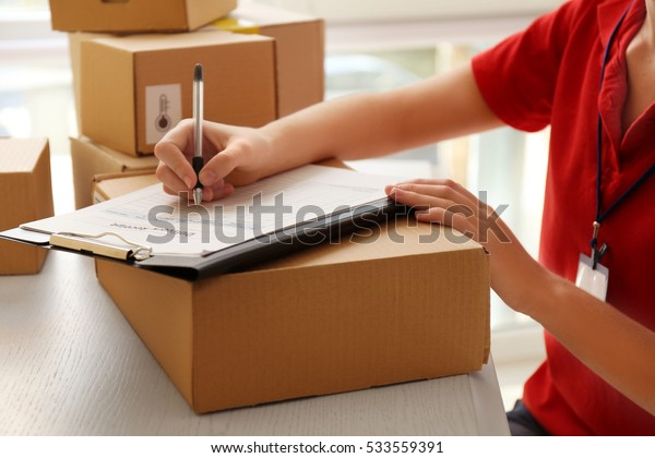 Courier hands writing in clipboard at table