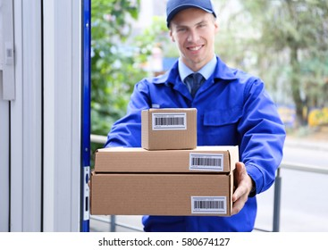 Courier holding packages in doorway