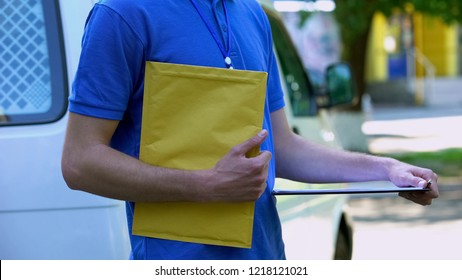 Courier holding yellow package and proof delivery form, documents shipping