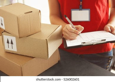 Courier making notes in delivery receipt at table