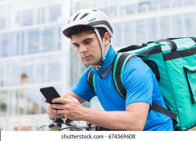 Courier On Bicycle Delivering Food In City Using Mobile Phone