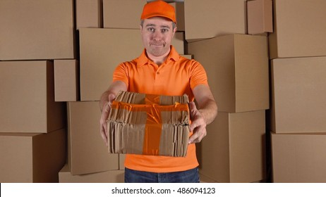 Courier in orange uniform delivering damaged parcel to customer. Brown cartons background. Flaw and unprofessional work concepts