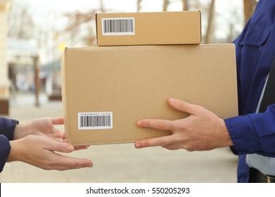 Courier with parcel in doorway, closeup (it's not real QR code)