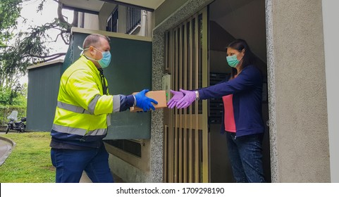 Courier in protective mask delivers parcel and gloves, customer in medical gloves receives box. Delivery service under quarantine, disease outbreak, coronavirus covid-19 pandemic conditions.