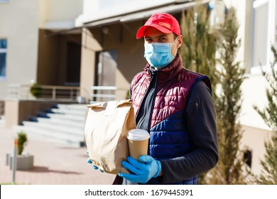Photo of Courier in protective mask and medical gloves delivers takeaway food. Delivery service under quarantine, disease outbreak, coronavirus covid-19 pandemic conditions.
