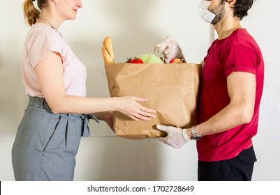 Courier in protective mask and medical gloves delivers takeaway food. Delivery service under quarantine, disease outbreak, coronavirus covid-19 pandemic