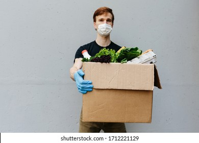 Courier in protective mask and medical gloves delivers takeaway food. Delivery service under quarantine, disease outbreak, coronavirus covid-19 pandemic conditions. Copy space