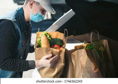 Courier in a protective mask and medical gloves takes out eco paper bags with groceries from the supermarket from the car trunk. Quarantine food delivery. Social distancing concept