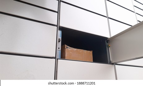 Courier Puts Cardboard Package Into Parcel Locker