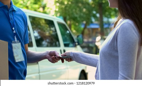 Courier receiving cash payment for cardboard parcel delivery, express shipping