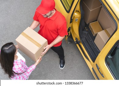 Courier In Red Uniform Takes The Delivery Package From Woman s Hands. Brunette Woman Takes Her Parcel In Cardboard Box From Polite Courier Standing Near The Yellow Delivery Track. Open Door Of The